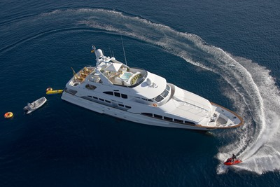Large white yacht surrounded by jetskis and other fun watercraft in the middle of the ocean.