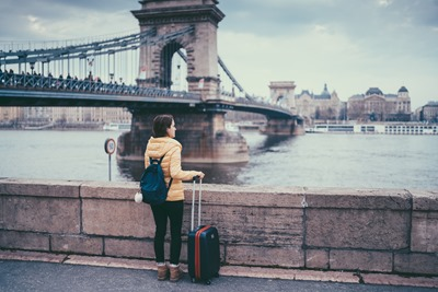 Young woman with suitcase staring at view