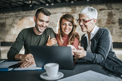 Young happy couple and their insurance agent working on a computer during a meeting in the office.