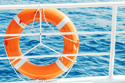 Ring life buoy on boat. Obligatory ship equipment. Orange lifesaver on the deck of a cruise ship.