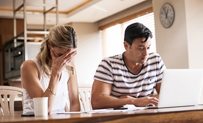 Shot of a couple looking stressed out while working on their finances at home