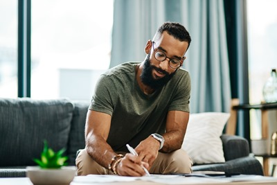 Shot of a young man going over his finances at home