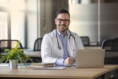 Happy male medical doctor portrait in hospital. Portrait of a male doctor with laptop sitting at desk in medical office. Portrait of a happy young doctor at medical office desk.