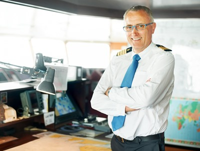 Smiling ship commander standing with his arms folded