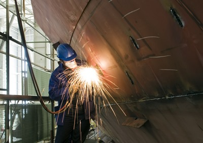 marine contractor working on a ship's hull while dry docked at a shipyard