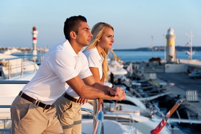 Horizontal color image of two people - attractive crew members -  standing on luxury yacht boat at harbor and looking at beautiful sunset.