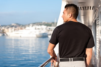 Horizontal rear view color image of male crew member standing on luxury yacht boat and looking on sea view during sunny day.