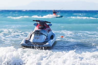 jetski sitting in the waves on a beach at a shore ex place