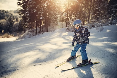 Little boy skiing on a winter day. The happy boy aged 7 is smiling. Sunny winter day.