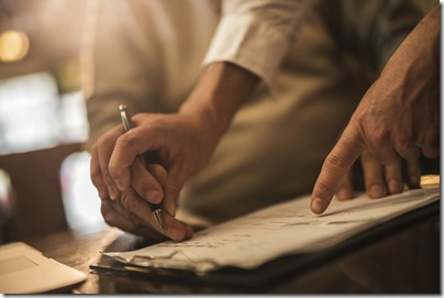 Unrecognizable senior signing a contract with help of financial advisor.